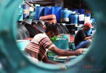 Pekerja menyelesaikan pembuatan tempat sampah dari drum bekas di Jalan Bandang, Makassar, Kamis (29/11/2018). (Sulselsatu/Moh Niaz Sharief)